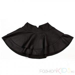 Детска къса черна пола с волани. Модерна черна поличка за момиченца, с много голяма периферия, изработена от плътна синтетична материя, която пада тежко. Коланчето е от трико с много добра еластичност и метална емблема, закопчава се с две копчета отпред.