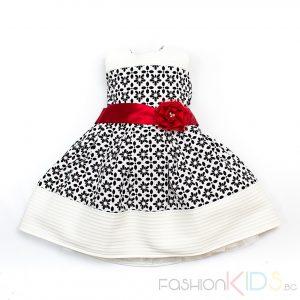 Чудесна детска рокля в класическа кройка с къс ръкав. Моделът се закопчава със скрит цип на гърба. Талията е украсена с красива ярко червена лента с голямо текстилно цвете и три сребристи перли. Роклята е изработена от плътна, леко еластична материя в черно и бяло. Отвътре е пришита подплата и тюл за повече обем. Ръкавът е сцепен на рамото и с декорация от камъчета.