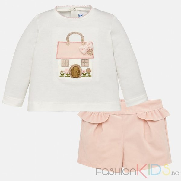 Комплект бебешки блуза и шорти. Блуза с дълъг ръкав и обло деколте. На гърба се закопчава с копчета, което улеснява обличането на Вашето дете. Дрехата е изработена от мека и еластична памучна тъкан. Декоративните елементи на блузата включват апликация с бродерия и малко метално лого с нежна джуфка. Къси панталонки с еластична лента на талията. Изработени от мека тъкан, с бастички отпред на колана, и декоративно набрано коланче с елегантен и класически вид.