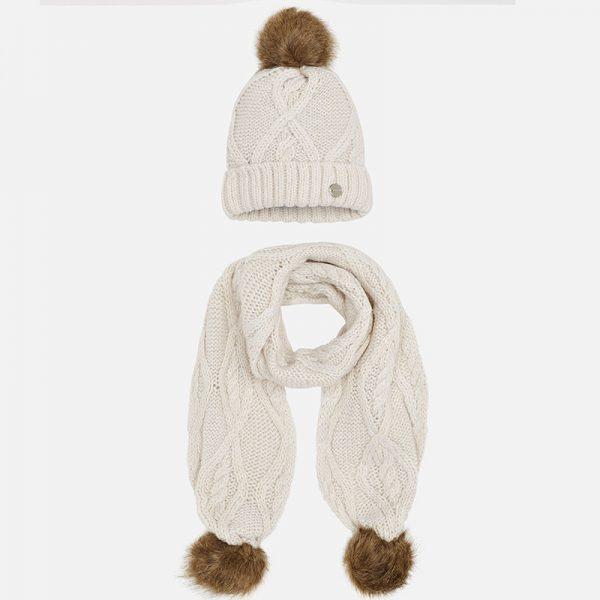 Детски комплект шапка и шал за момиче, изработени от мека, топла, дебела плетена тъкан. Моделът е с имитация на кожени помпони и елементи. Малко кръгло лого в края на шапката.