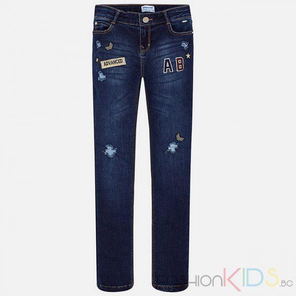 Детски дънки с големи джобове на гърба. Моделът е с модерен дизайн, прорези, емблеми и бродерия. Еластична талия на кръста, цип и закопчаване на копчето. Моделът е с 5 джоба.
