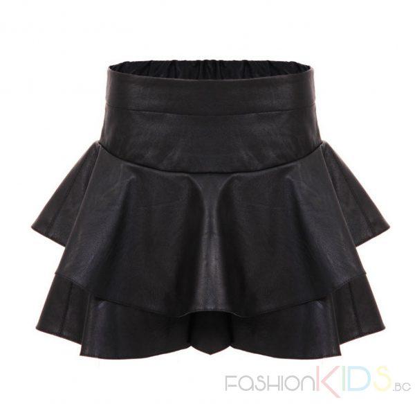 Детска пола-панталон с волани. Модерна черна поличка за момиченца, с много голяма периферия, изработена от плътна синтетична материя имитираща естествена кожа, която пада тежко. Коланчето е широкоо с ластик.