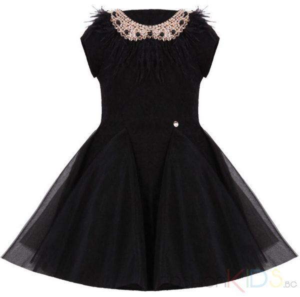Стилна детска рокляот нежна висококачествена матери и тюл в черен цвят. Роклята е с визиянапринцеса - с кройкапо тялотов горната част над талията, добавен е нежен тюл в същия цвят. Много разкроена и с обем под талията с богато наслоен тюл в същия цвят. На гърба се закопчава със скрит цип, а на яката има красива декоративна украса с черни пера и блестящи камъни, на талията има дискретно, малко кръгло лого. От вътрешната страна над талията има памучен хастар. Дизайна на роклята придава кукленскавизия на малките Ви принцеси. Подходяща е за всякакви празнични поводи, като официална бална рокля.