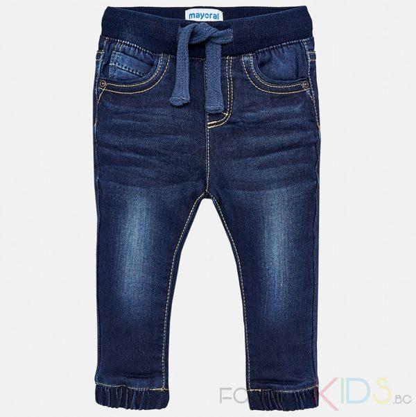 Бебешки дънки за момче с протъркан ефект, стеснени наглезена. Моделс 5 джоба. Малка кръгла кожена емблема с лого над задния джоб. Изтъркан и износен ефект на крачолите отпред. Удобен модел за игри и разходки.Дънкитеимат регулируема, еластична лентас шнур за регулиране на размера в талията.