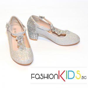 Детски официални обувки за момиче в сребристо на ток с коригираща каишка с ефектна лента с брокатени цветенца и естествена стелка.