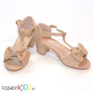 Детски официални отворени обувки за момиче в златисто на ток с ефектна панделка с камъни и блестящ брокатен ефект, коригираща каишка и естествена стелка.