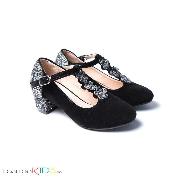 Детски официални велурени обувки за момиче в черно с блестящ брокатен ток и коригираща каишка със същият ефект
