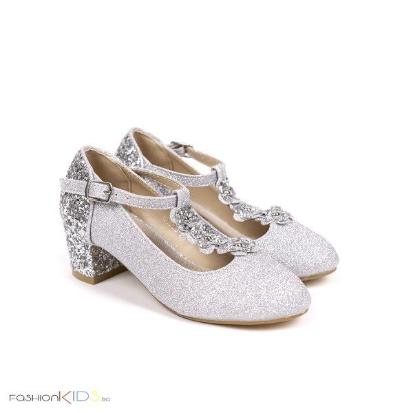 Детски официални обувки за момиче в сребристо с блестящ брокатен ток и коригираща каишка със същият ефект