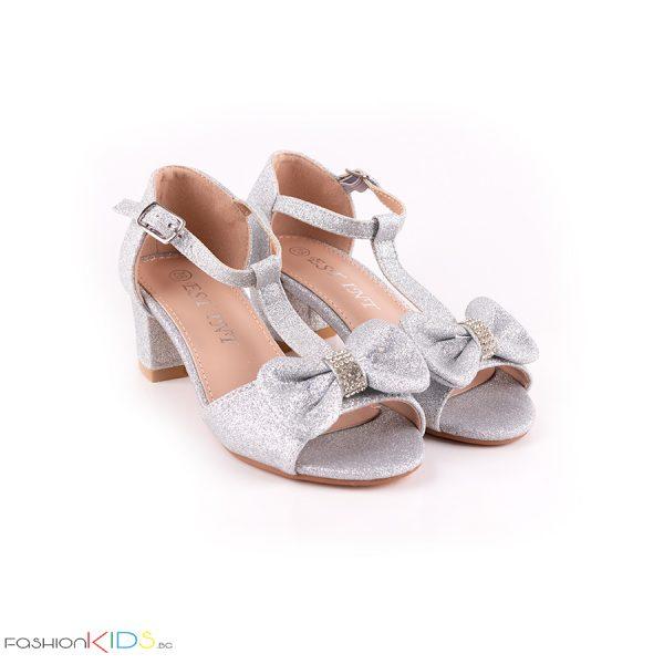 Детски официални отворени обувки за момиче в сребристо на ток с ефектна панделка с камъни и блестящ брокатен ефект, коригираща каишка и естествена стелка.